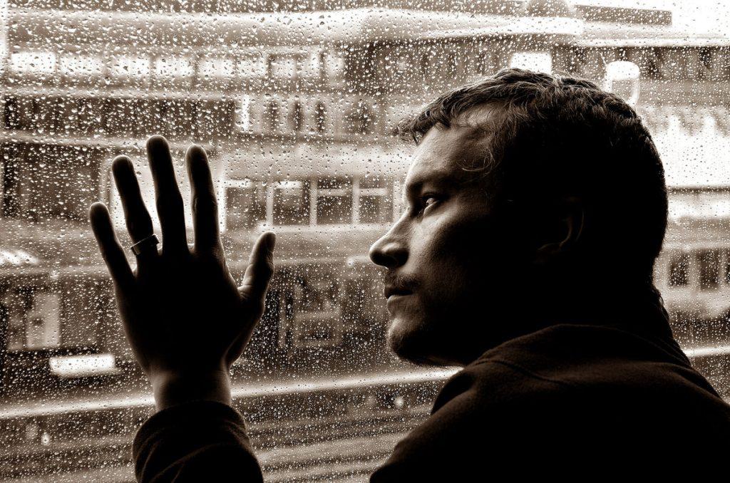 Парень смотрит на дождь из окна