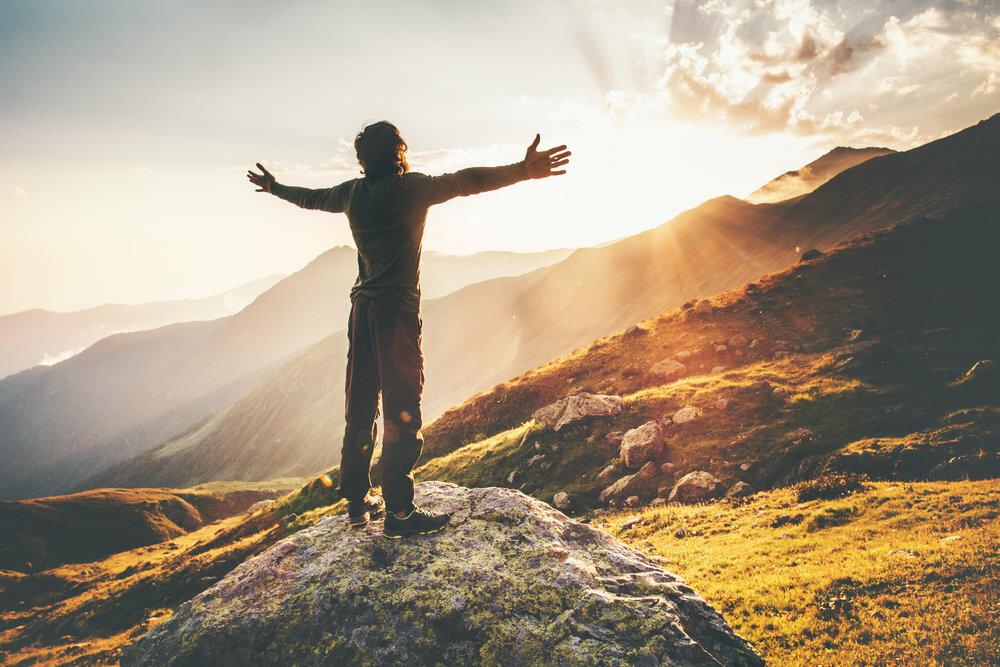 Человек раскинул руки на фоне рассвета в горах